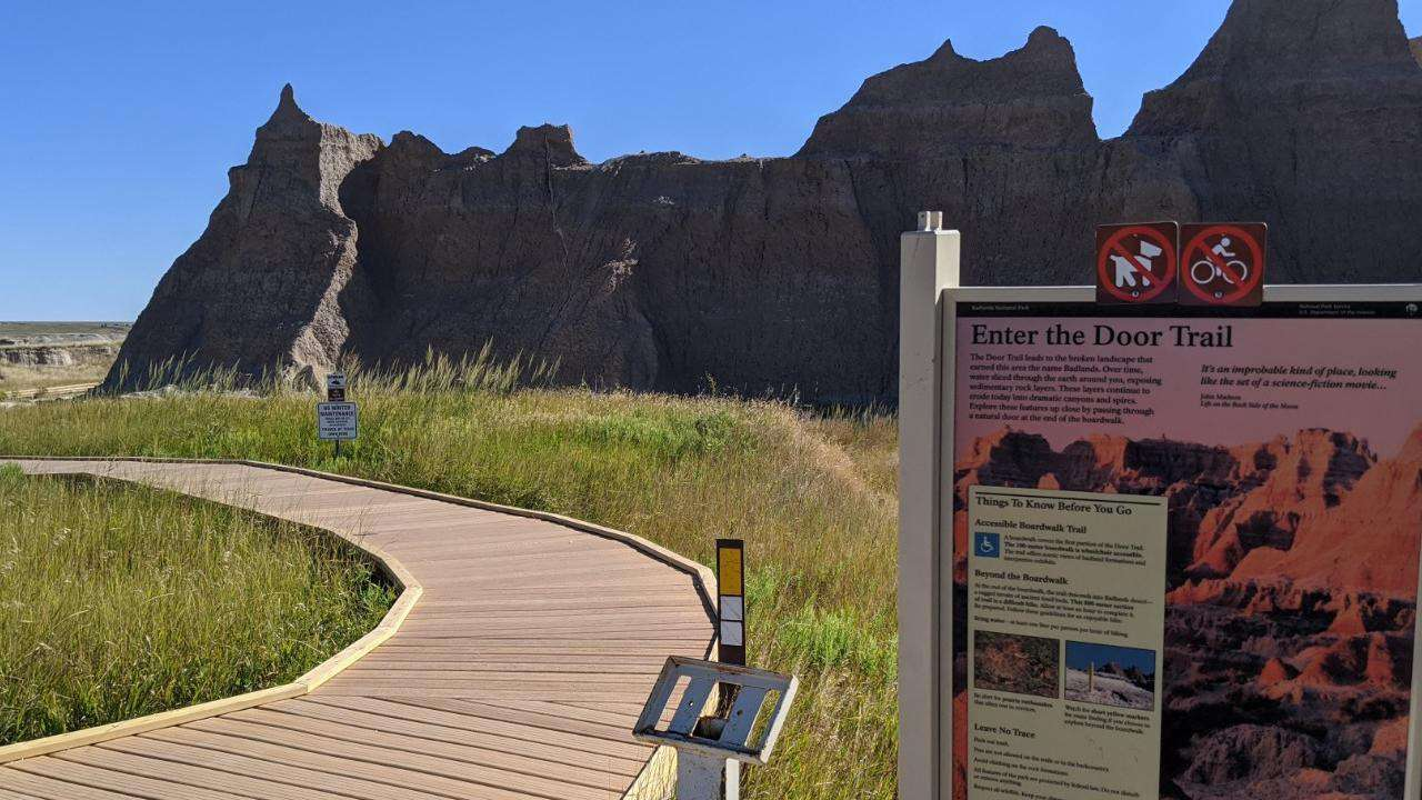 curving boardwalk trail in Badlands National Park with a sign explaining the trail