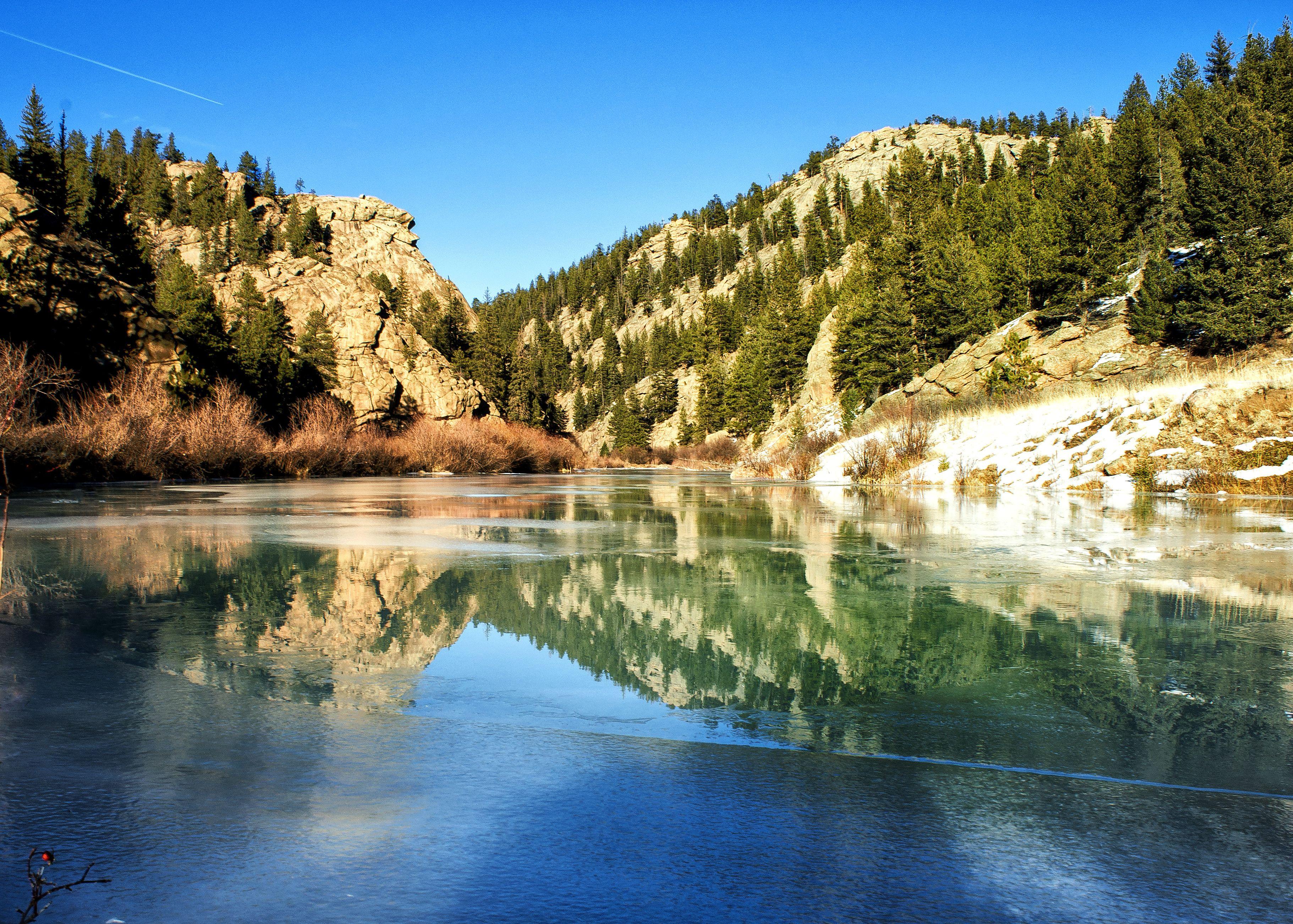 Montañas que se reflejan en el hielo y el agua en el cañón Elevenmile, Colorado