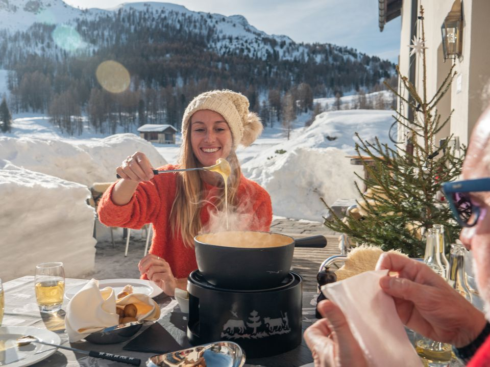 Family eating Swiss cheese fondue in the Alps in winter