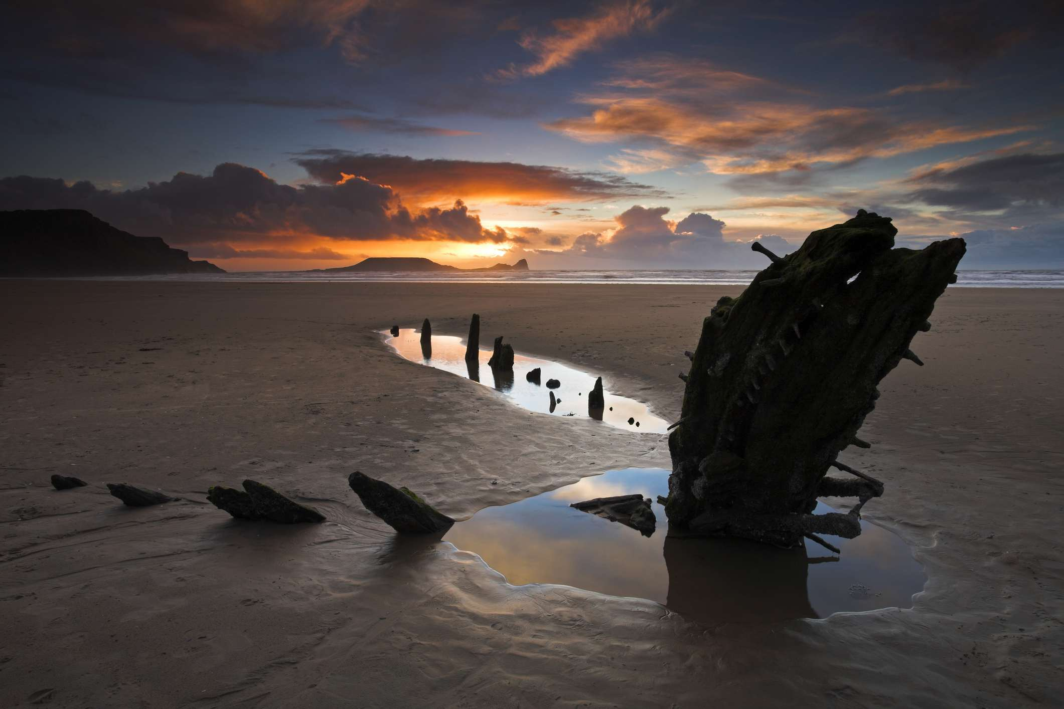 Beachside at Rhossili Bay with the wreck of the Helvetia buried in the sand, and Worm's Head on the horizon, Gower Peninsula, near Swansea, Wales, United Kingdom, Europe
