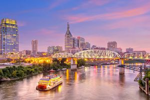 Illuminated boat on the Cumberland river at dusk with the Nashville Skyline and one of the bridges lit up.
