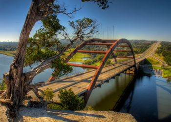 An early morning, Austin, Texas view of the Pennybacker Bridge or '360 Bridge' as it is more commonly known. The bridge spans across Lake Austin and connects the Capitol of Texas Highway (Loop 360). You can see downtown Austin off to the left on the horizon.
