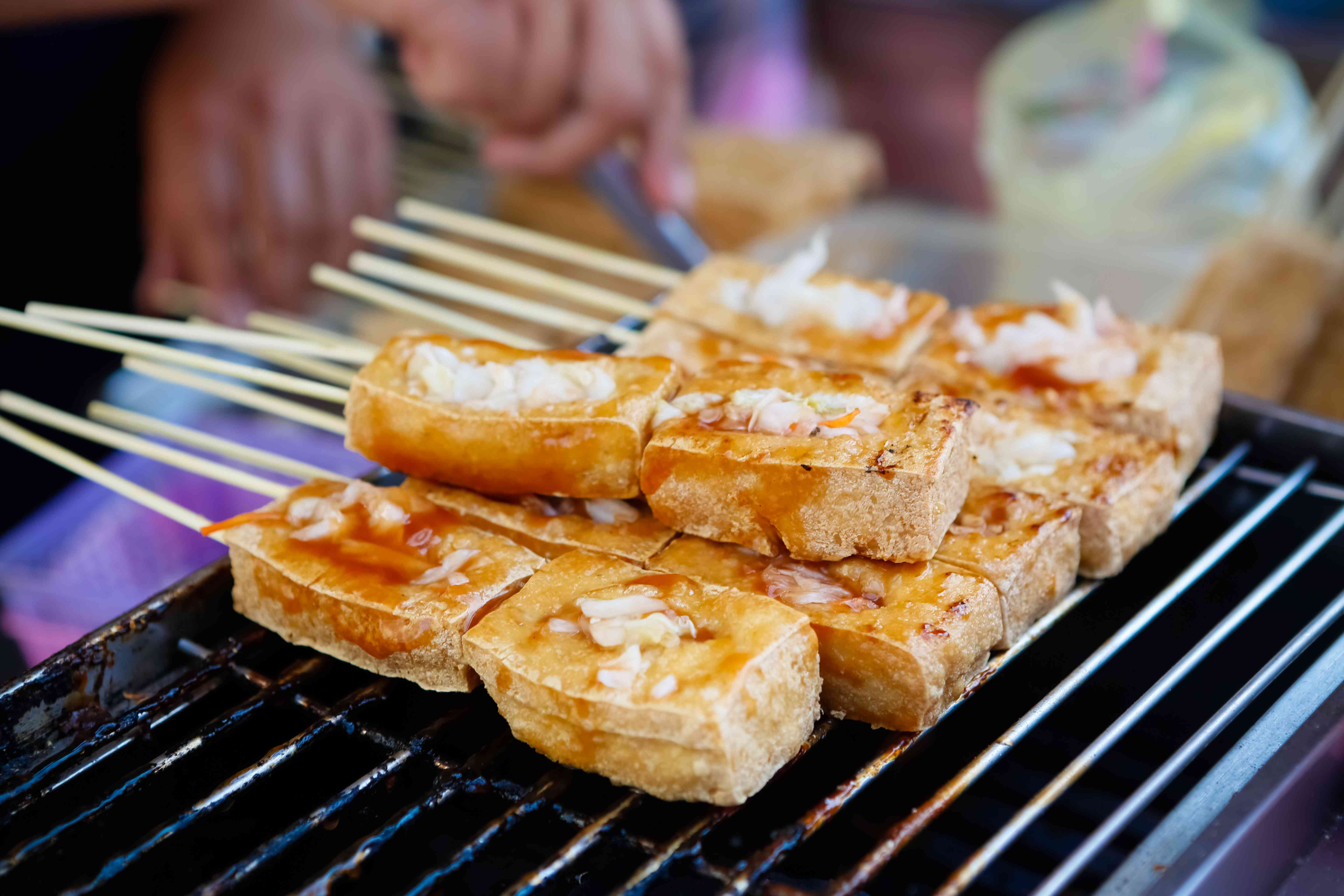 skewers of stinky tofu on a grill