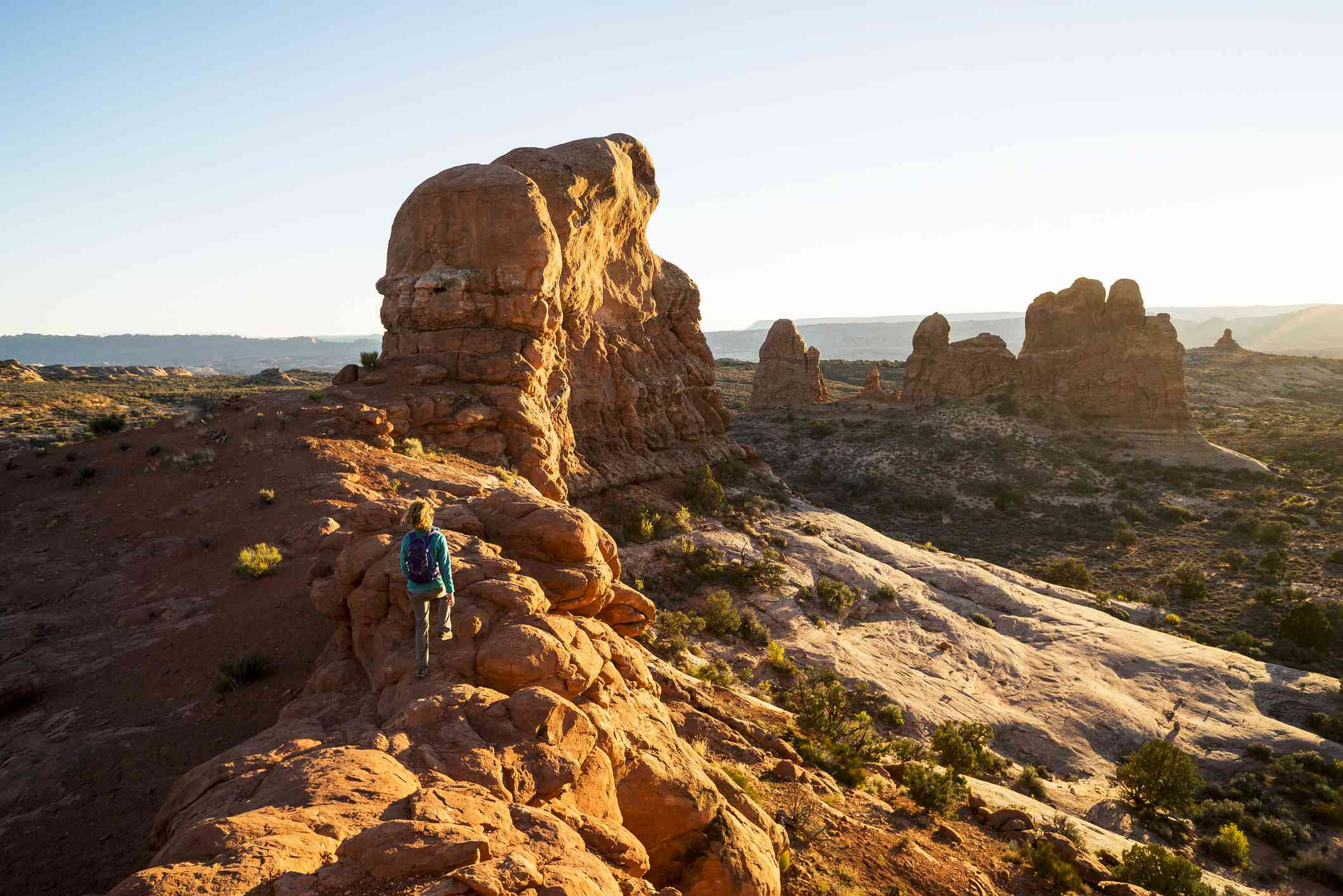 A woman hiking a scenic trail in Arches National Park.
