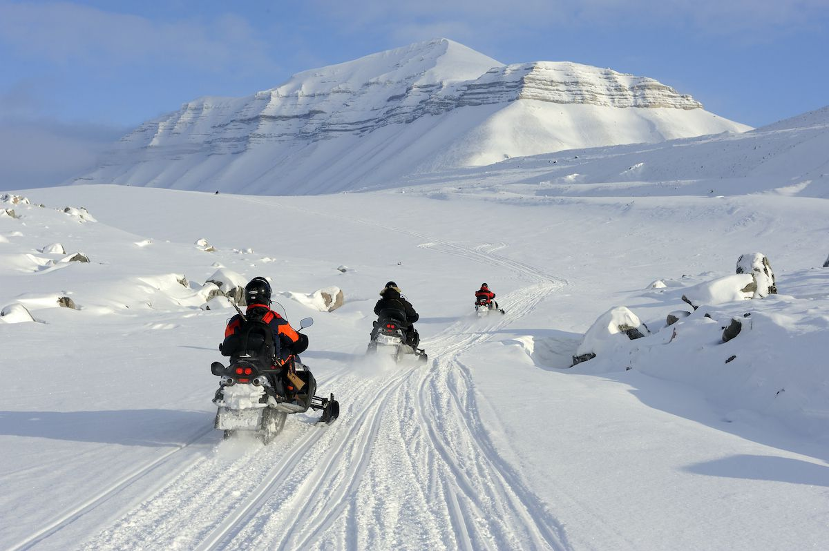 Three snowmobiliers follow a trail into the Norwegian wilderness