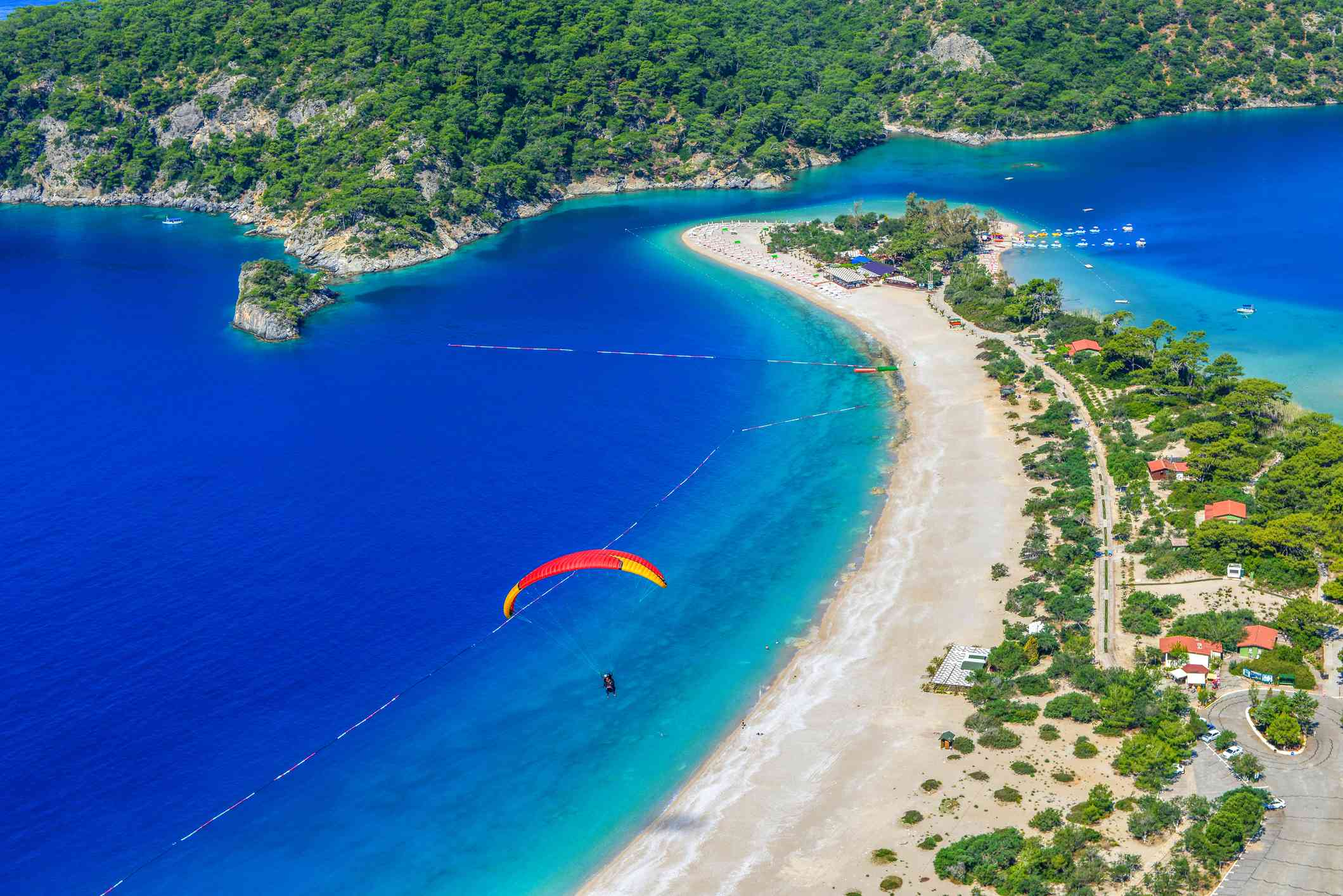aerial shot of bright blue sea with a long white beach and a red paraglider in the sky