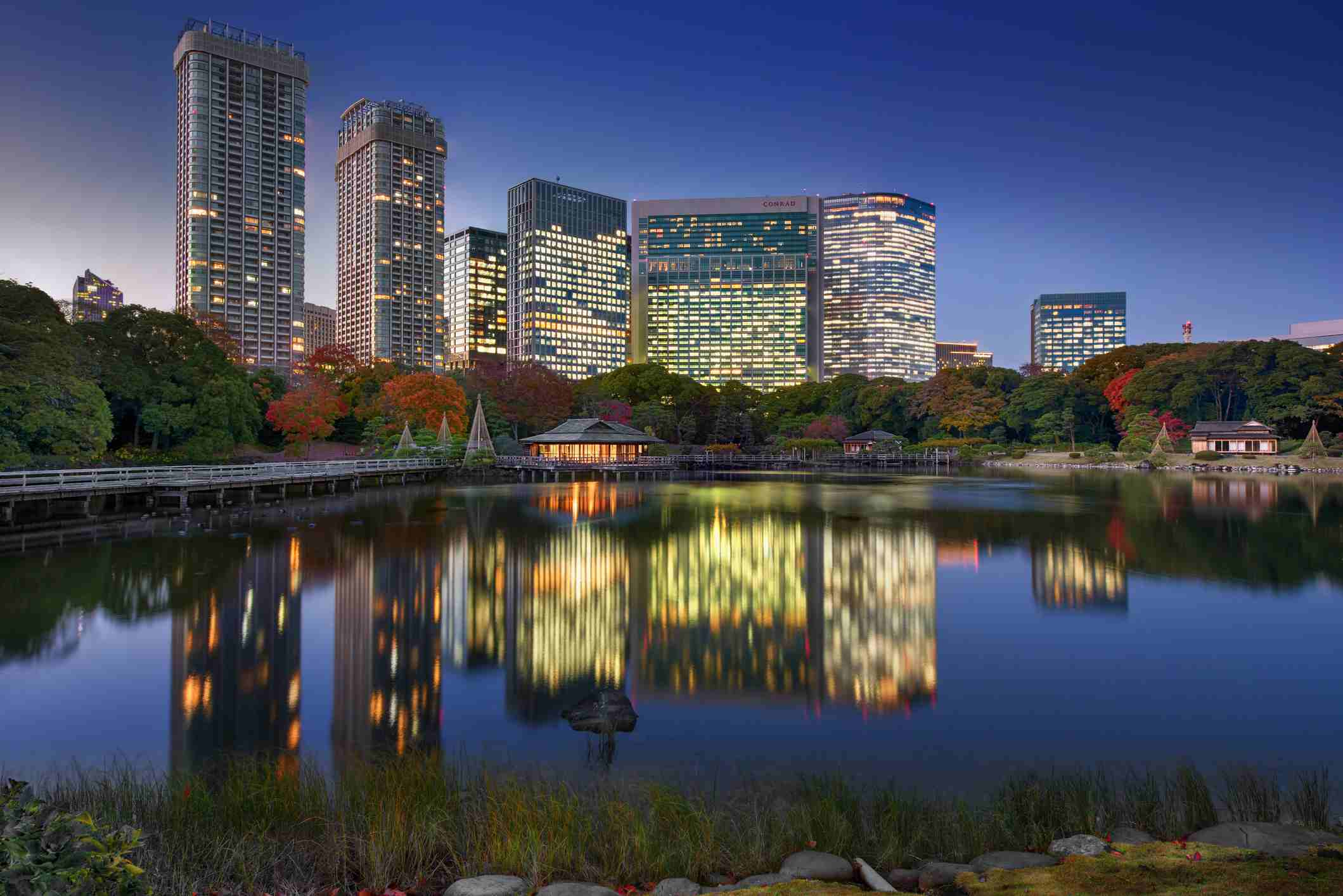 Hamarikyu Gardens' seawater pond reflects a traditional Japanese teahouse and Shiodome skyscrapers in autumn colors at dusk.