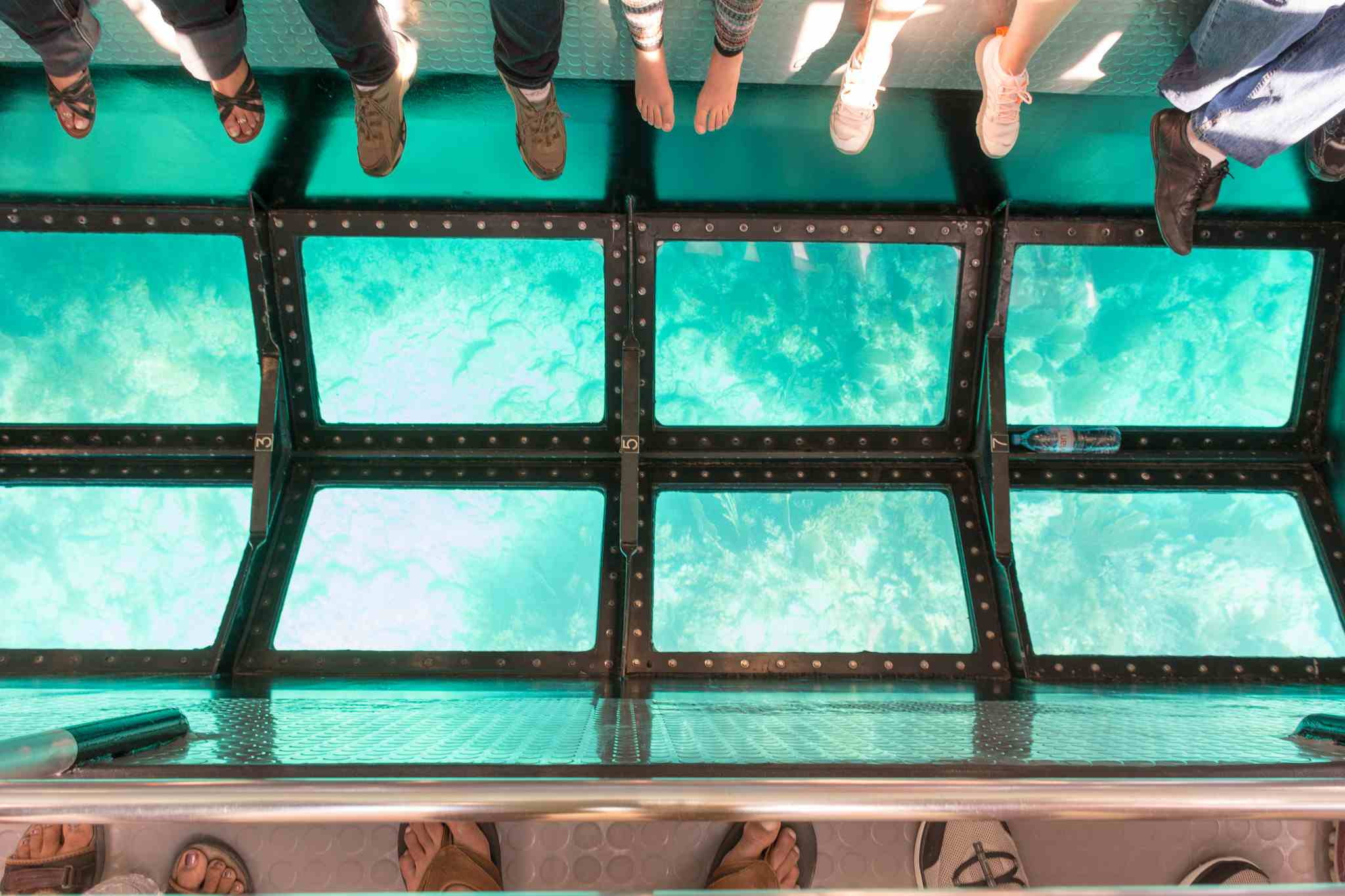 Peoples feet and the glass bottom of a tour boat