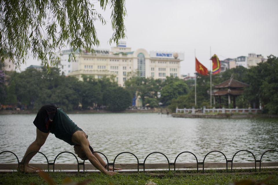 Yoga practitioner in front of the Hoan Kiem Lake, Hanoi, Vietnam