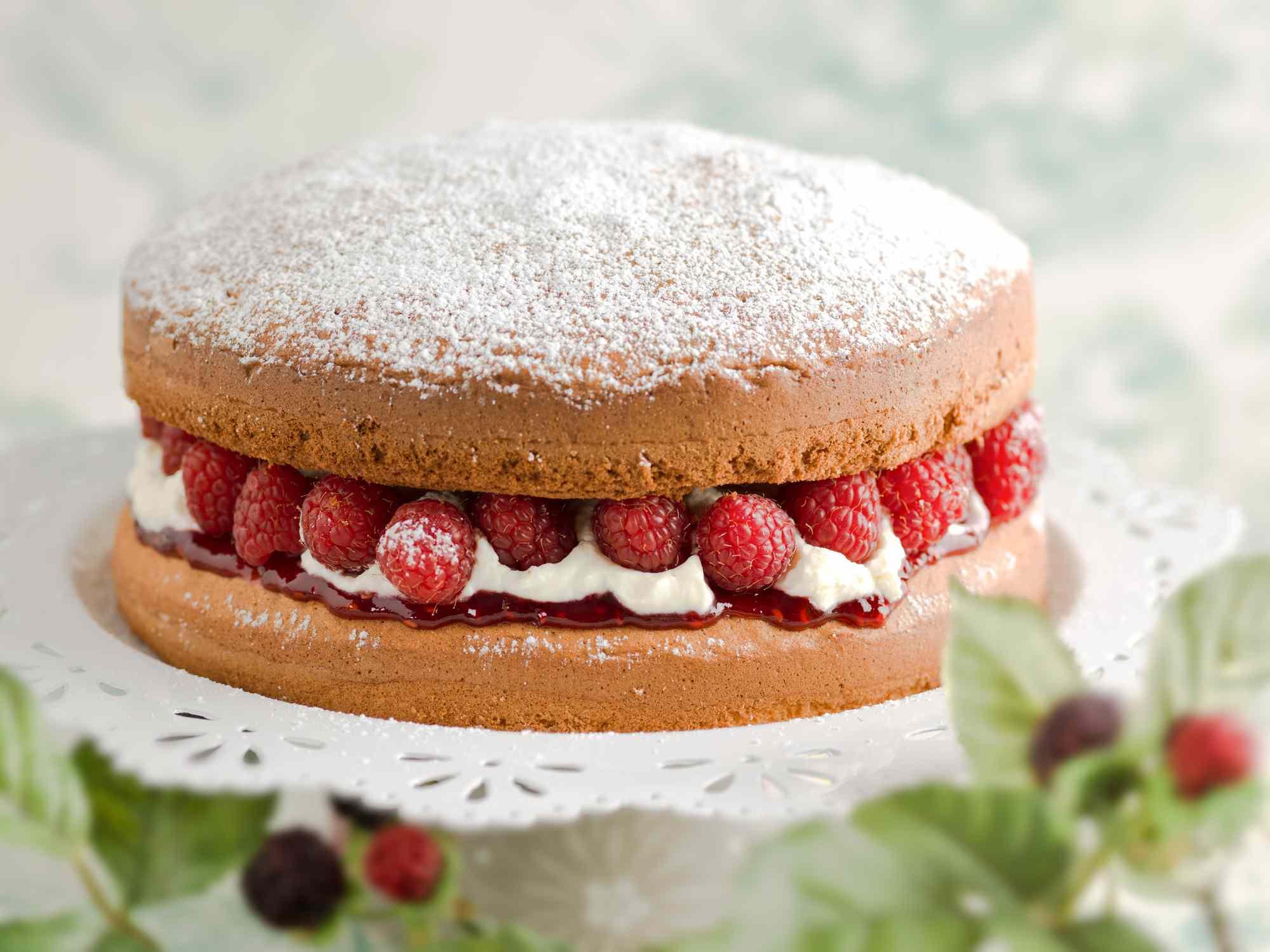 Victoria sponge cake filled with fresh whipped cream, rasberries and jam on white platter.