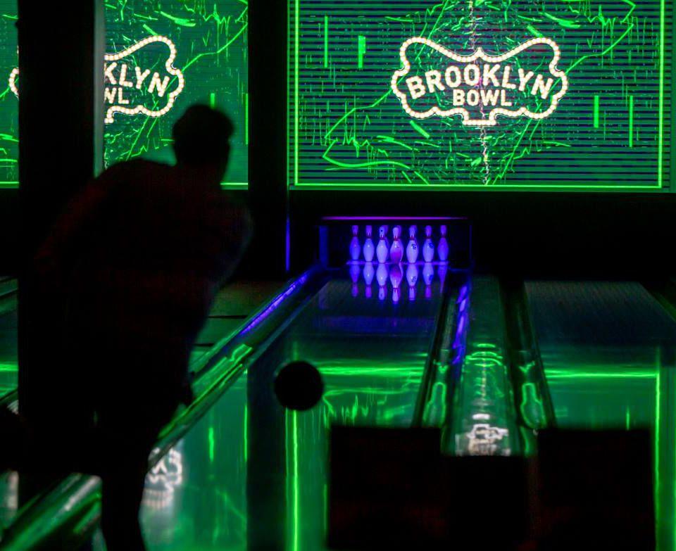 Someone bowling at glow in the dark bowling at Brooklyn Bowl Las vegas
