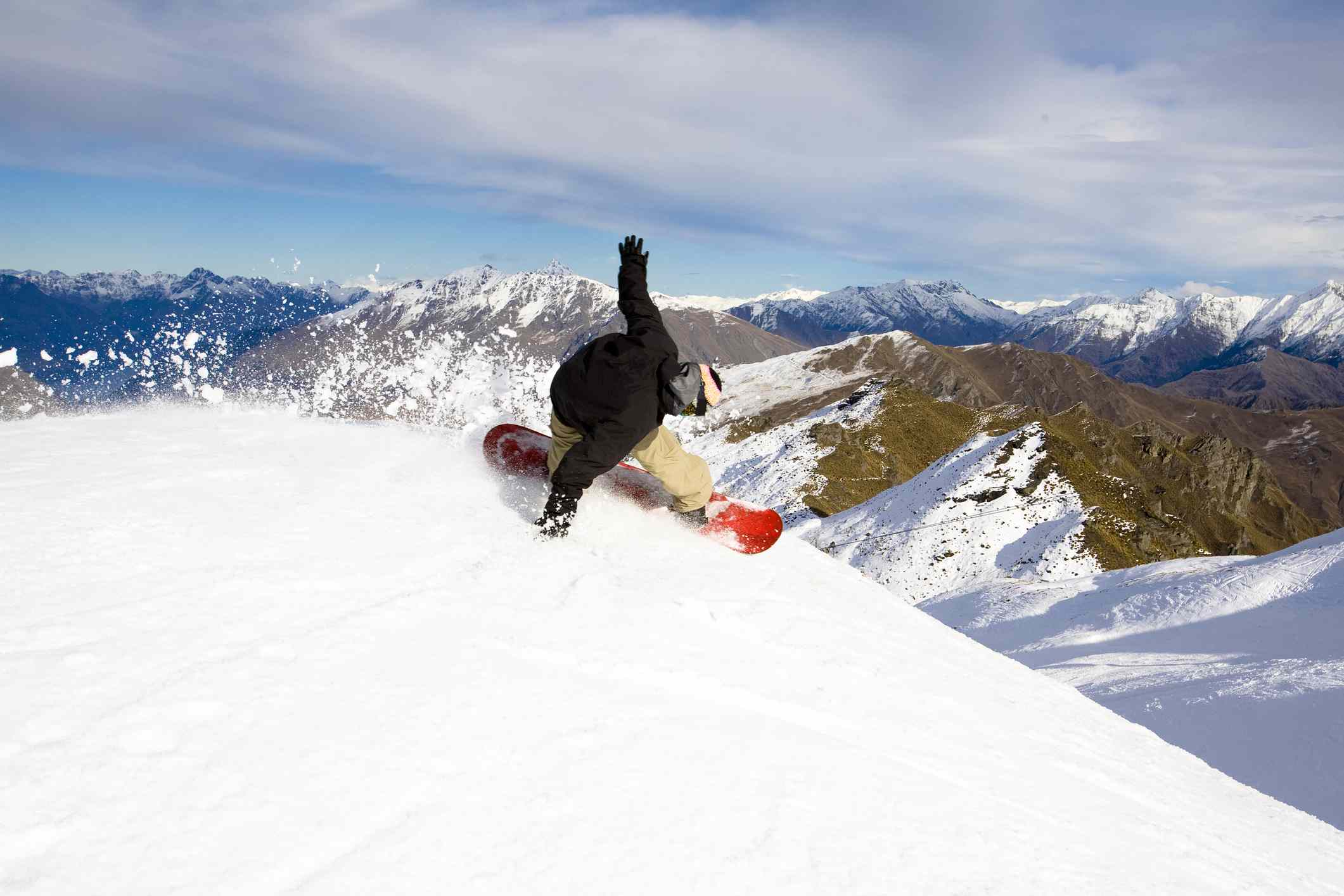 snowboarder on snow covered slope in snowy mountains