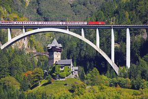 Passenger train on a bridge passing by Unterfalkenstein Castle in Austria.