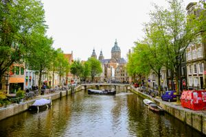A canal lined with green trees and colorful buildings