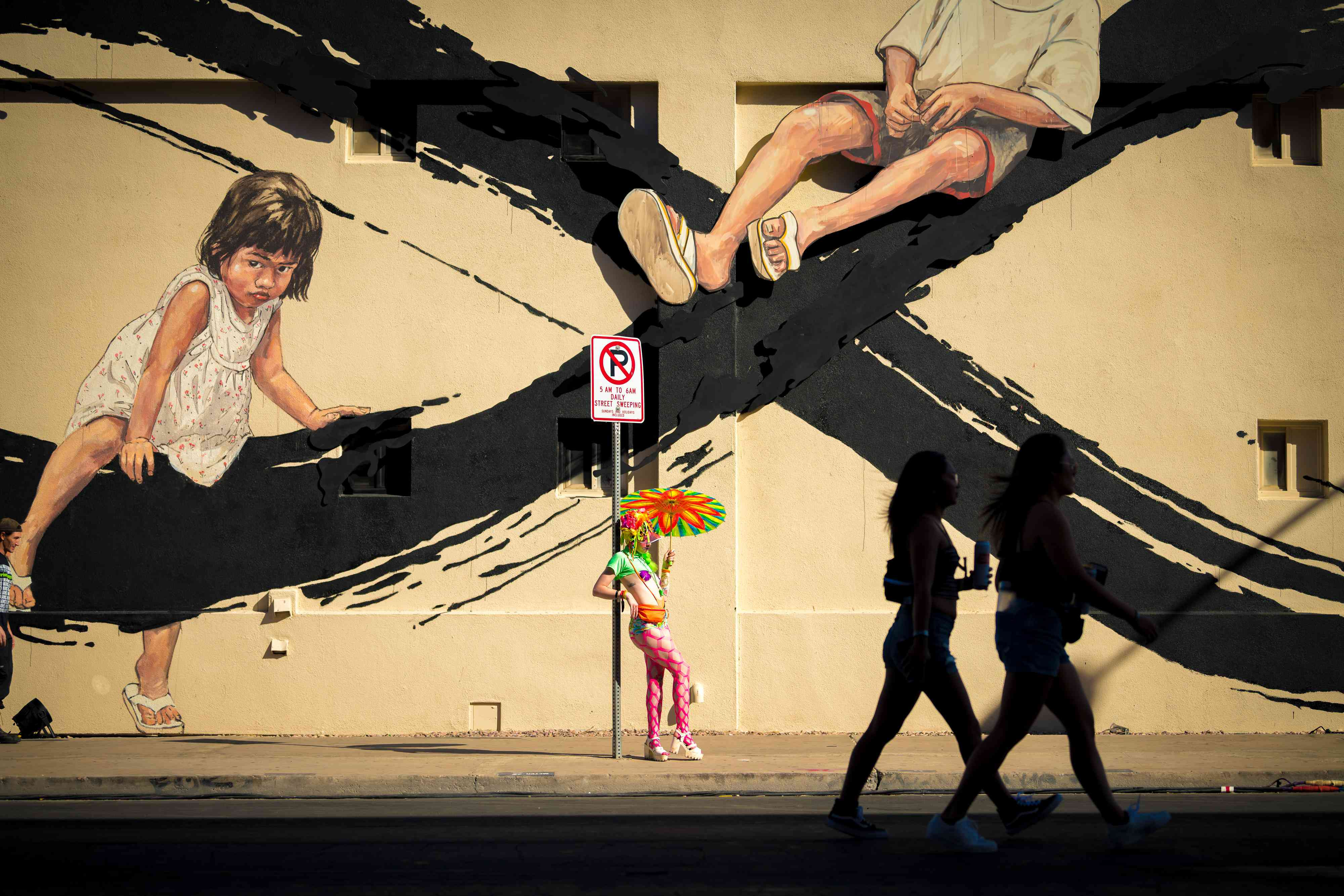 Two women in silhouette walking past a parson in a colorful outfit standing in front of a wall mural