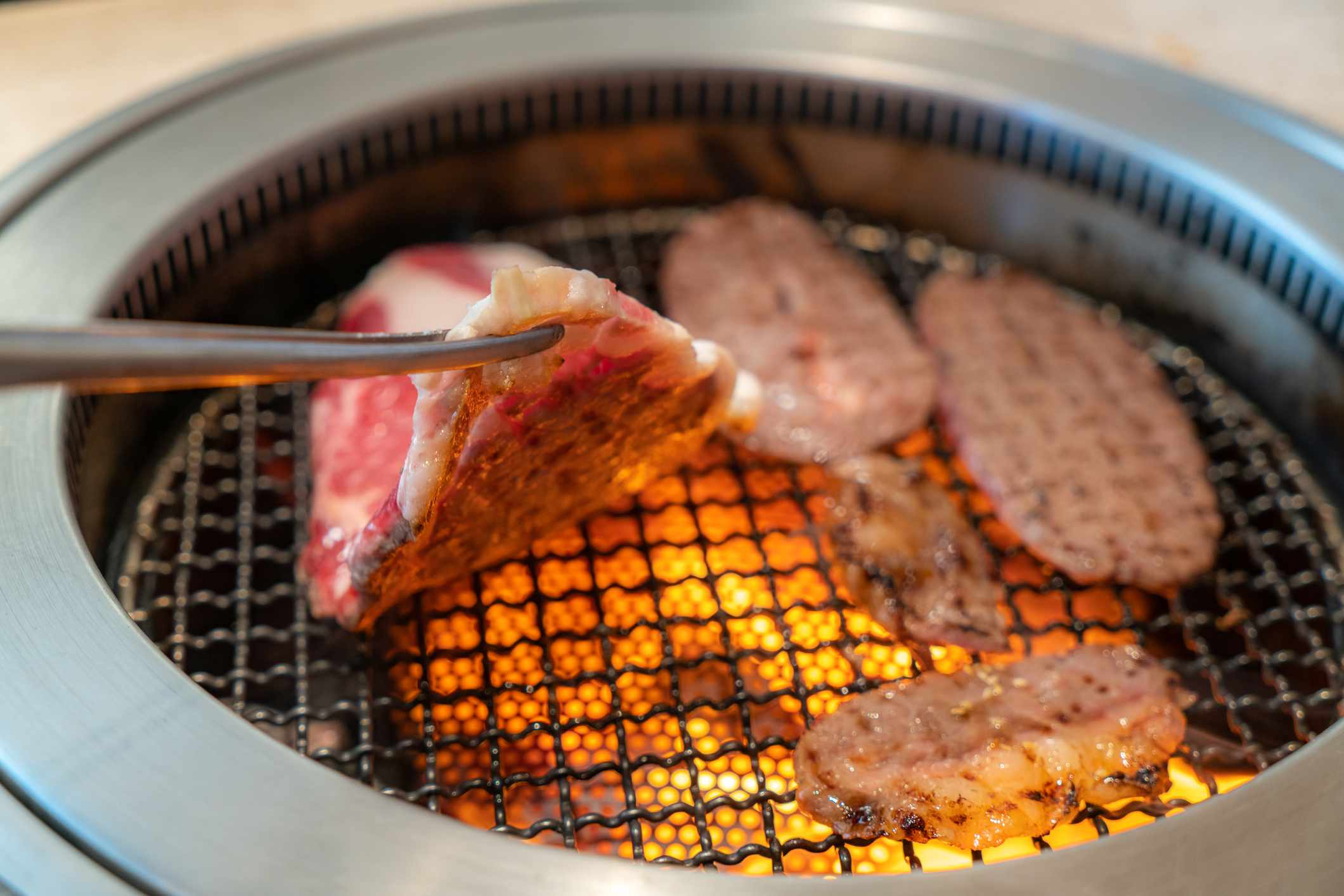 pieces of meat on a small japanese charcoal grill