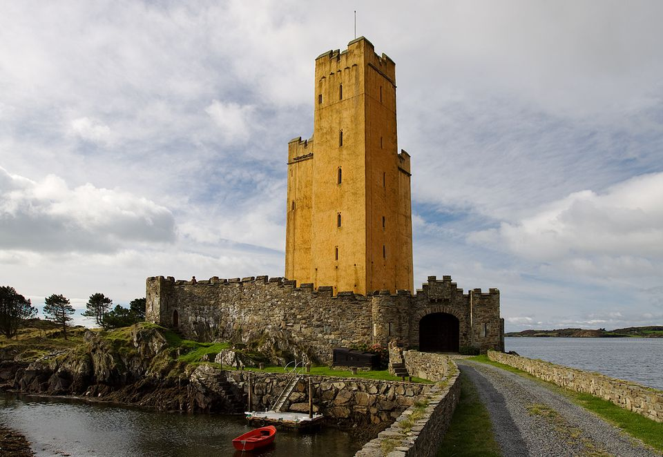 orange tower castle at end of causeway