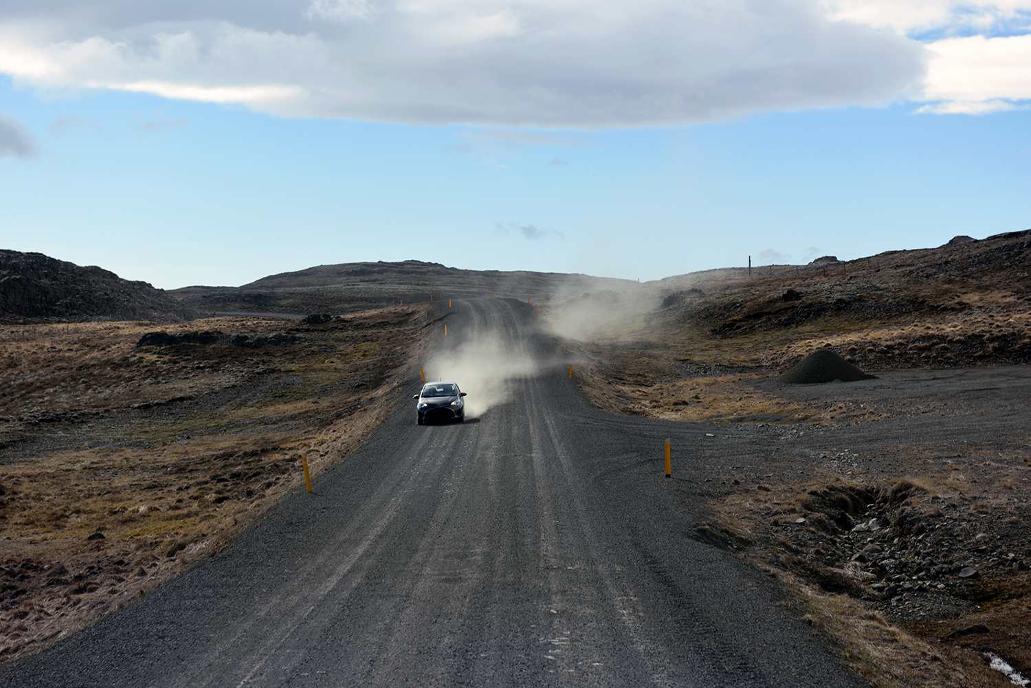Car driving down a dusty road