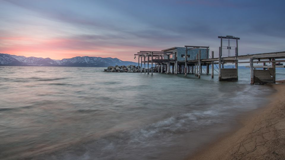 Long Exposure of Beautiful Lake Tahoe Sunset and Snowy Mountain Peaks Taken from Nevada Beach, South Lake Tahoe