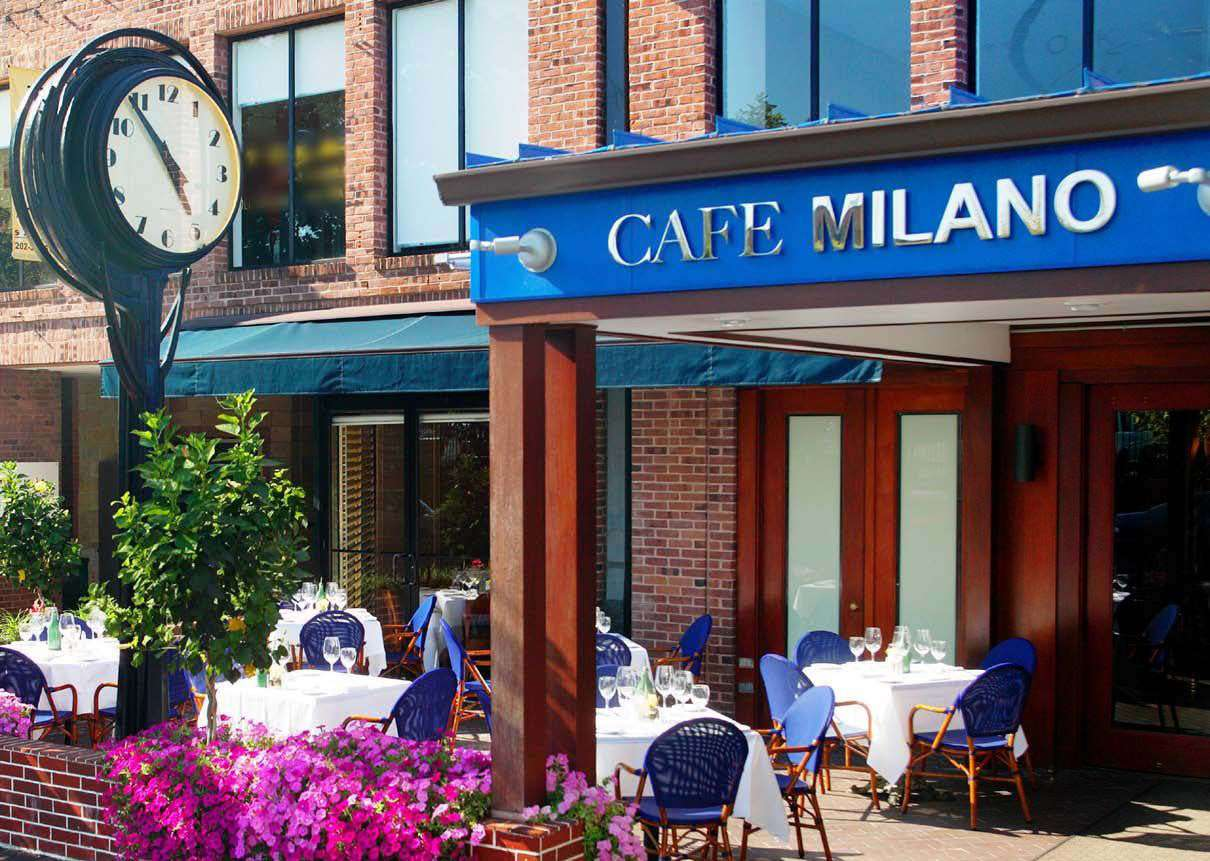 Patio seating and a small clock stand at Cafe Milano