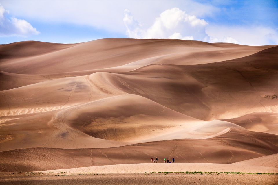 People standing at the bottom of massive sand dunes