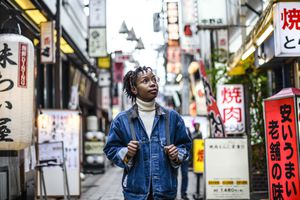 Black woman in her 20s with braided hair and glasses looking up at signs on a Tokyo street