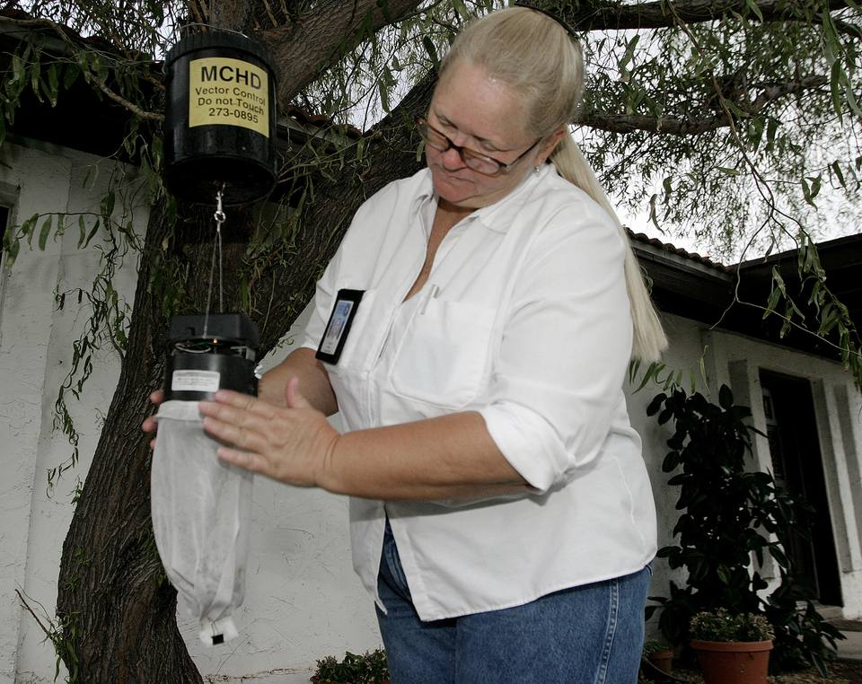 A Maricopa County Vector Control officer removes a mosquito trap near a home in Gilbert.
