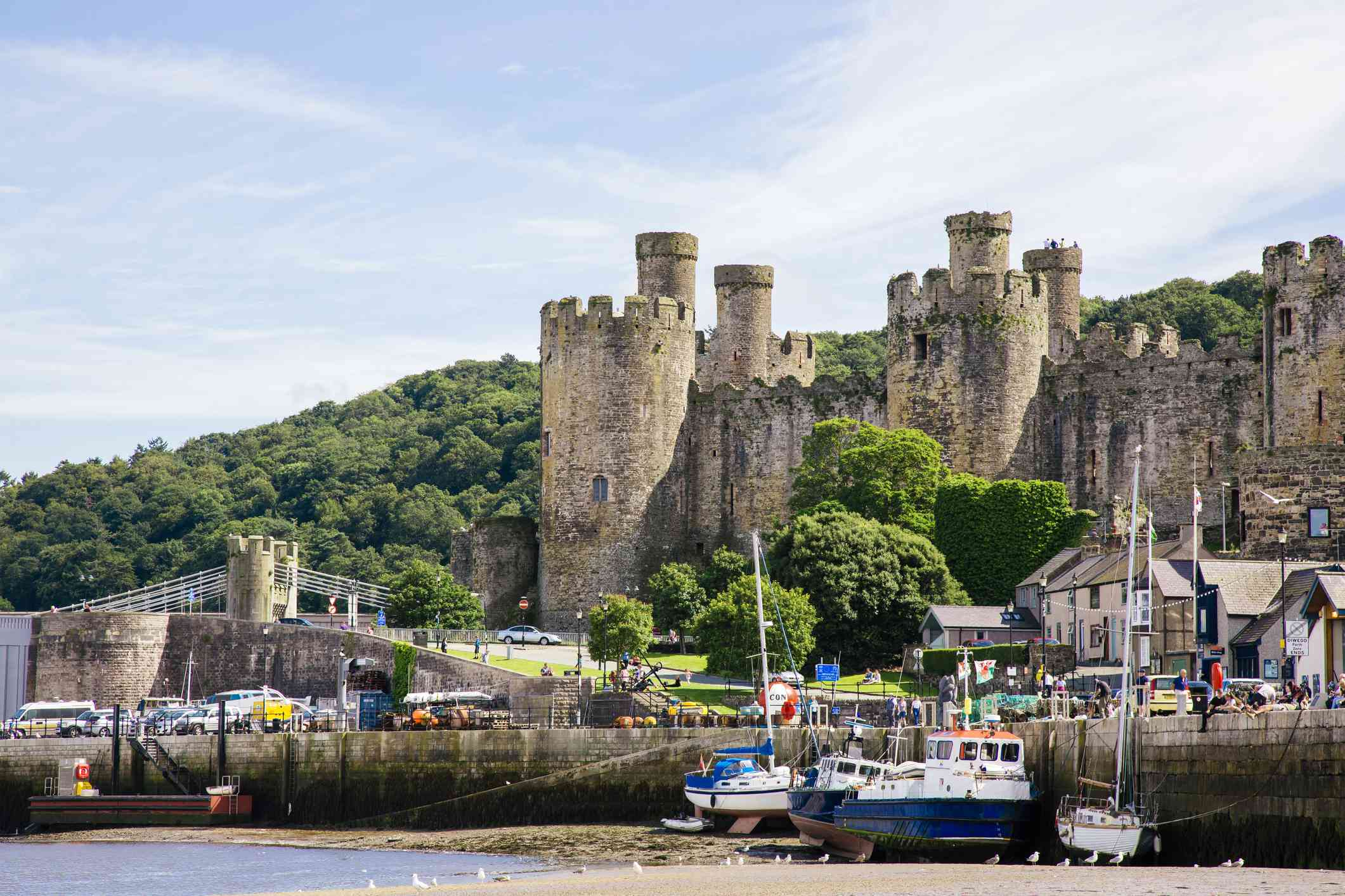 boats in a harbor below Conwy Castle in North Wales