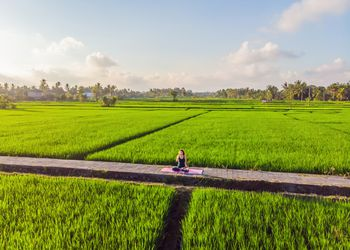 Woman practicing yoga outdoor in the rice fields during a yoga retreat in Bali
