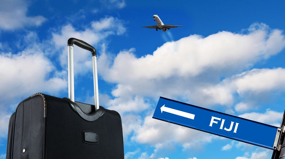 Low Angle View Of Direction Sign Beside Luggage With Airplane Flying In Sky