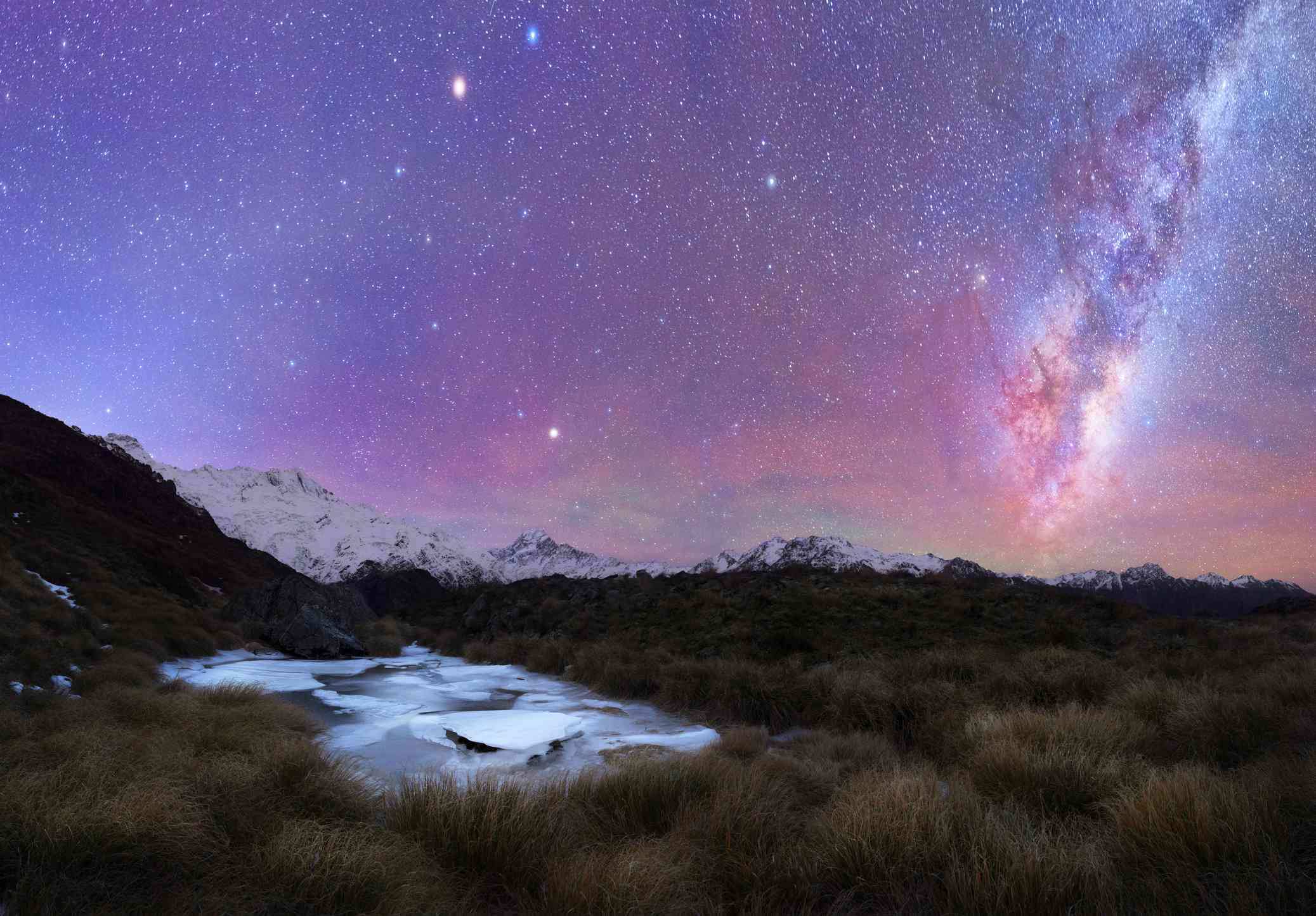 purple night sky with stars and constellations and snow-covered mountains