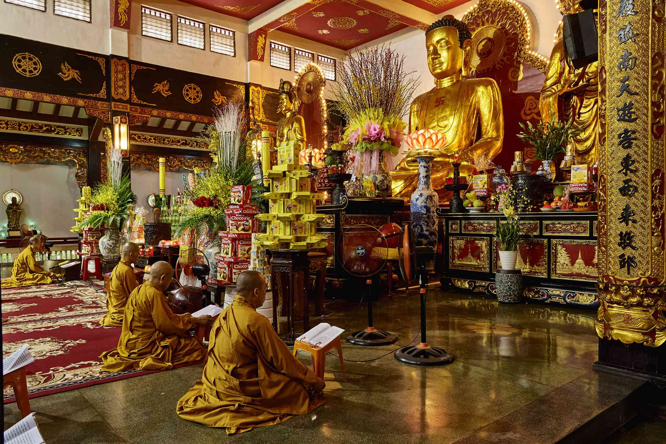 monks praying in in an ornate temple with a statue of buddha