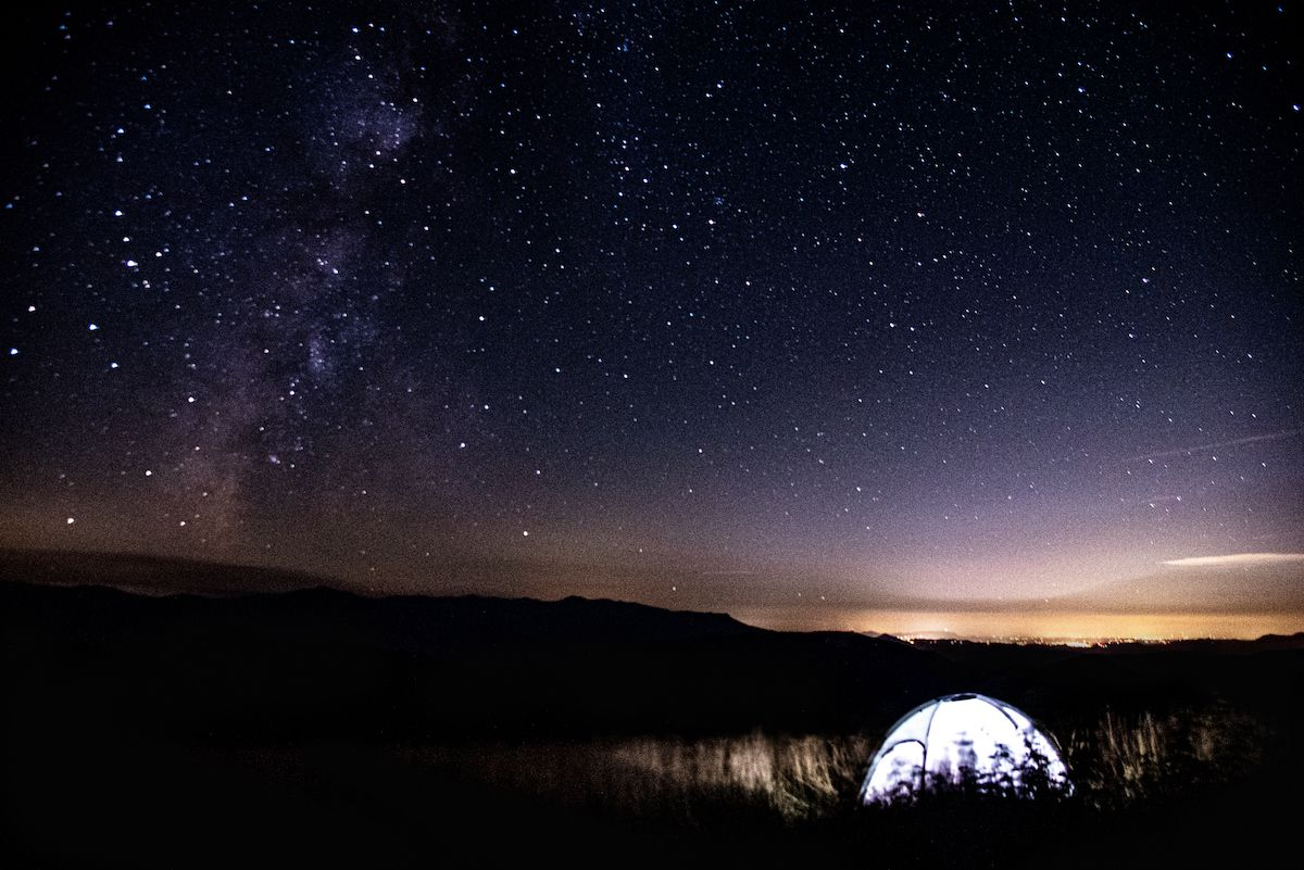 An illuminated tent sits in a mountain meadow with thousands of stars overhead