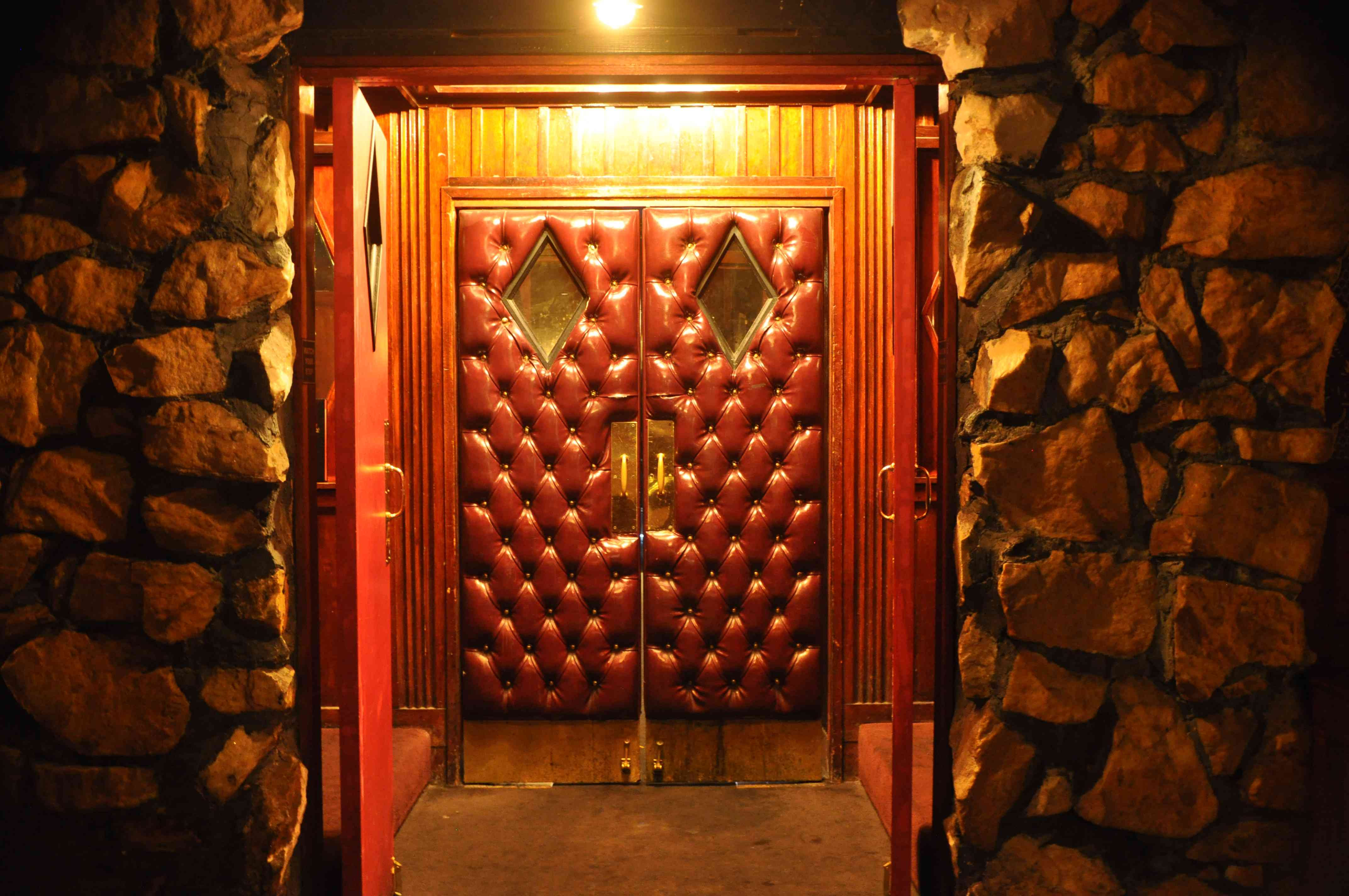 Two closed red-quilted leather doors with behind a set of open, red wooden doors