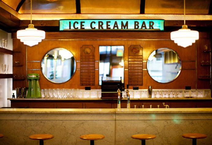 Marble bar with stools and a sign on the back wall that says
