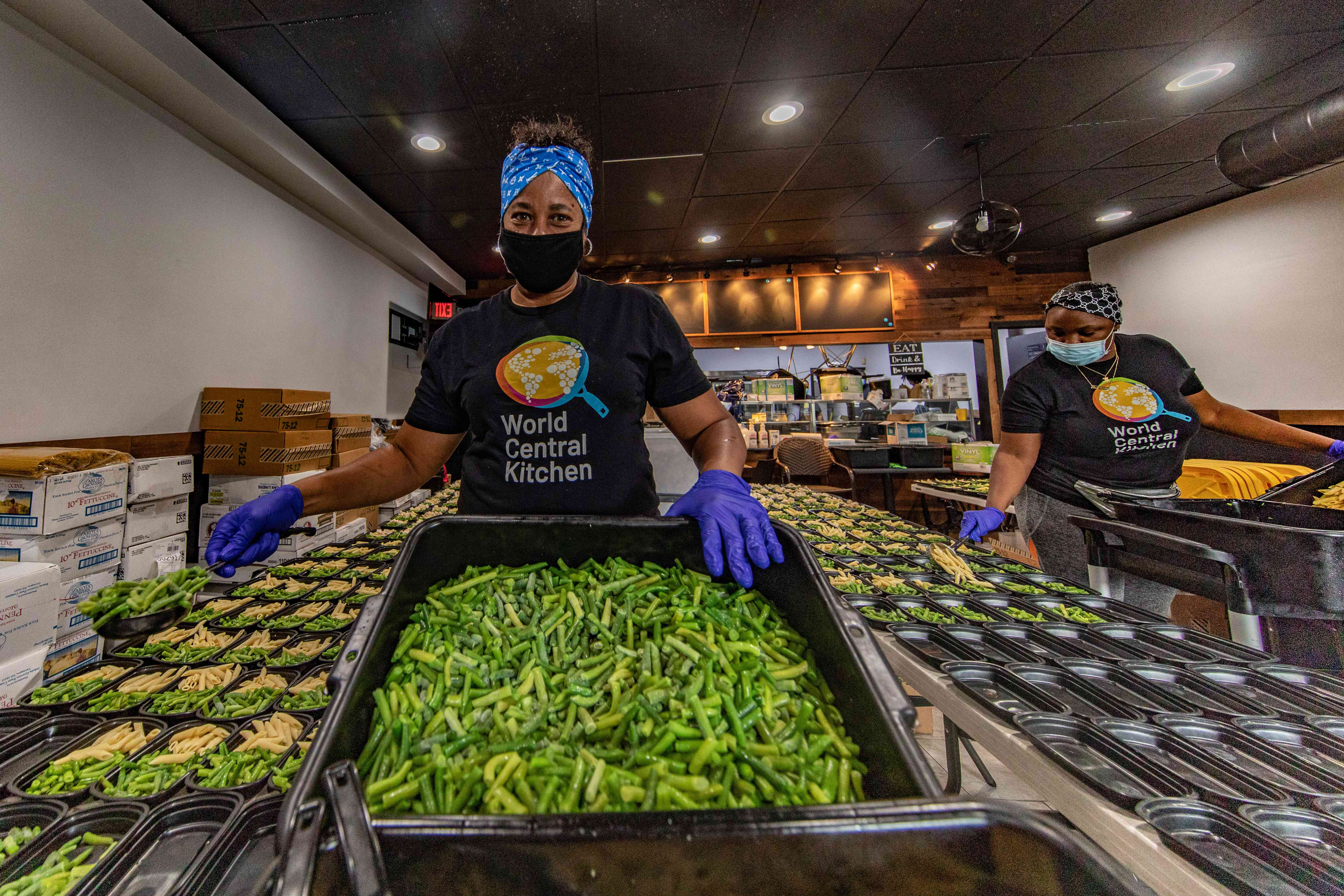 A volunteer holding a huge batch of green beans for meals
