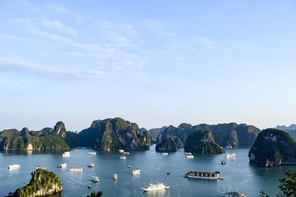 Wide shot of several votes cruising Ha Long Bay