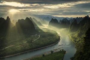 Sun breaking through cloudy sky mountain landscape in China