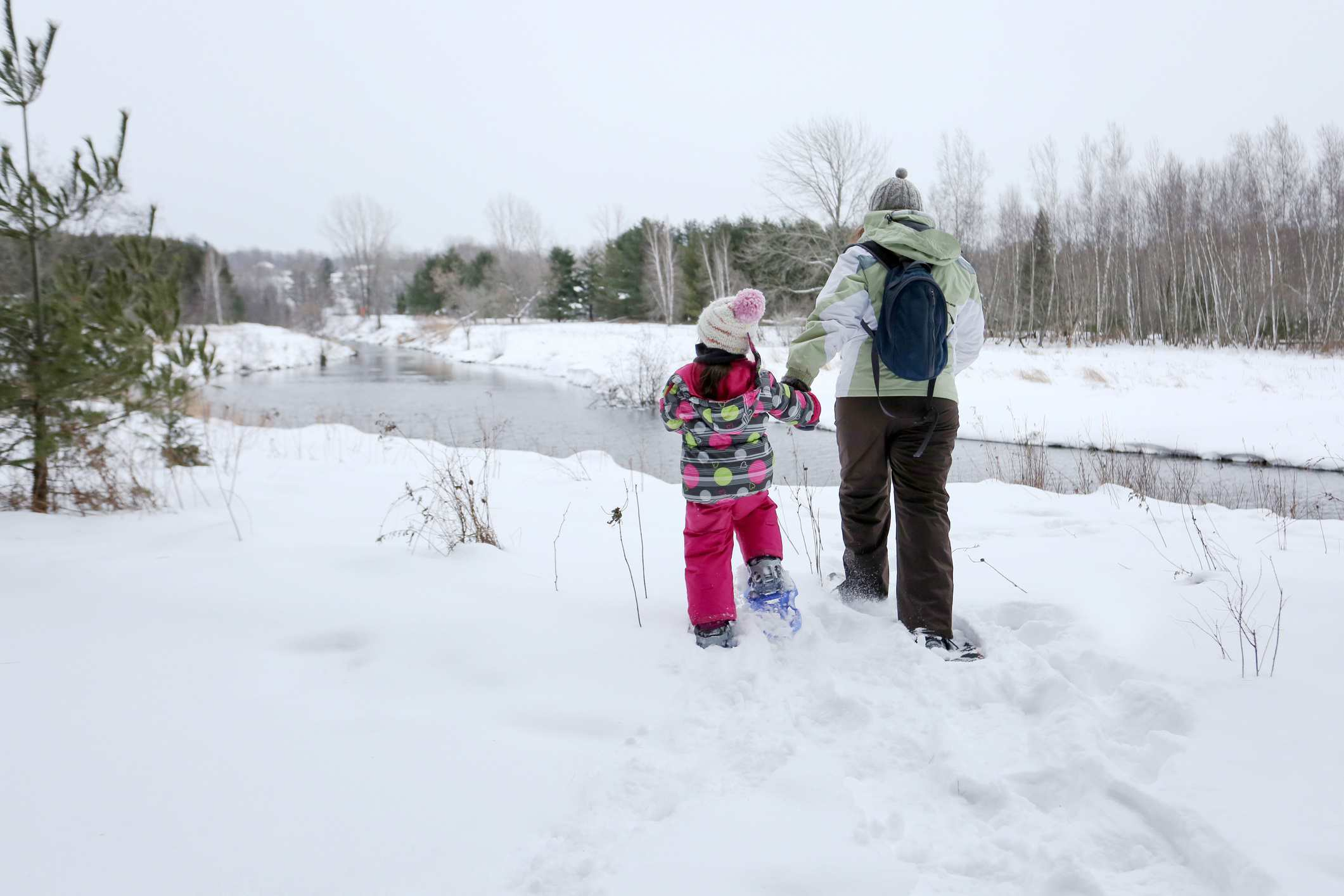 Mother and her little girl snowshoeing