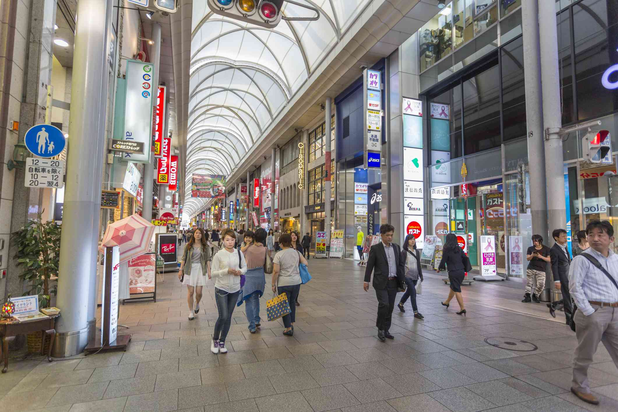 people walking under a covered shopping arcade in japan