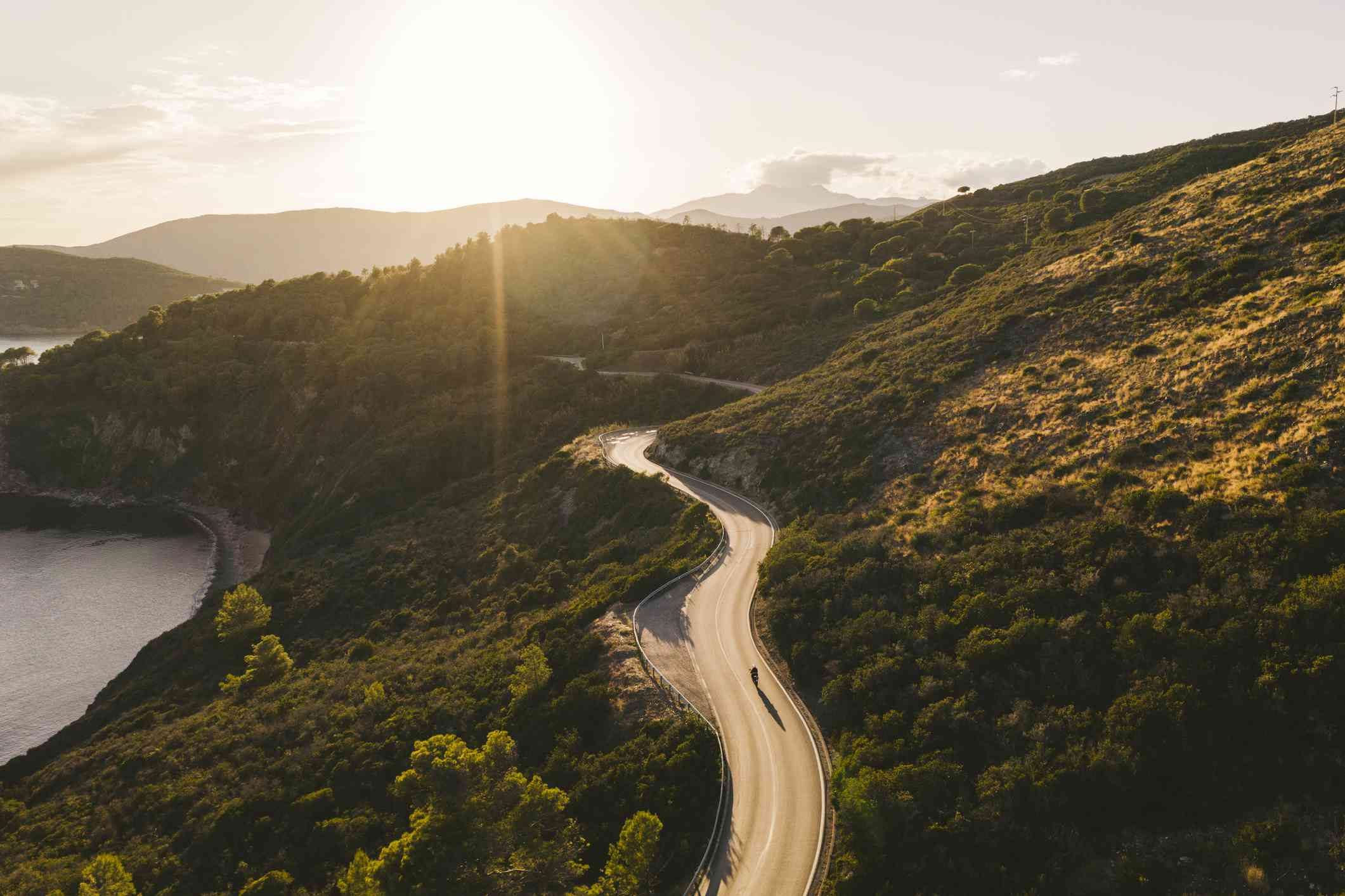 Biker on coastal road in Elba Island, Tuscany against the sun, aerial view with drone