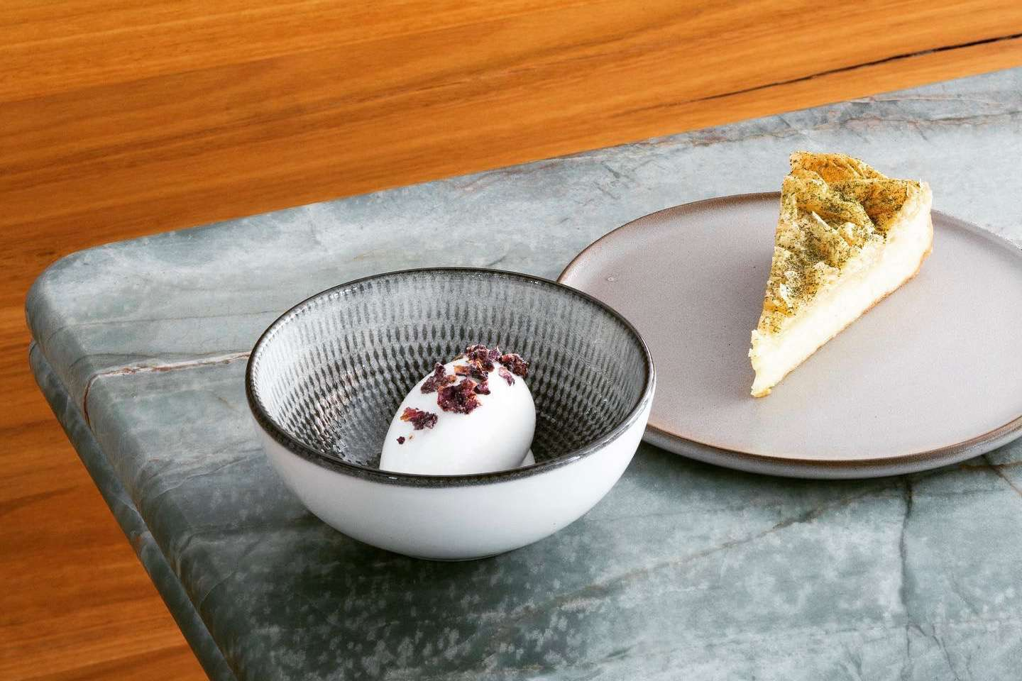 Two plates on marble bench with custard pie and white chocolate sorbet