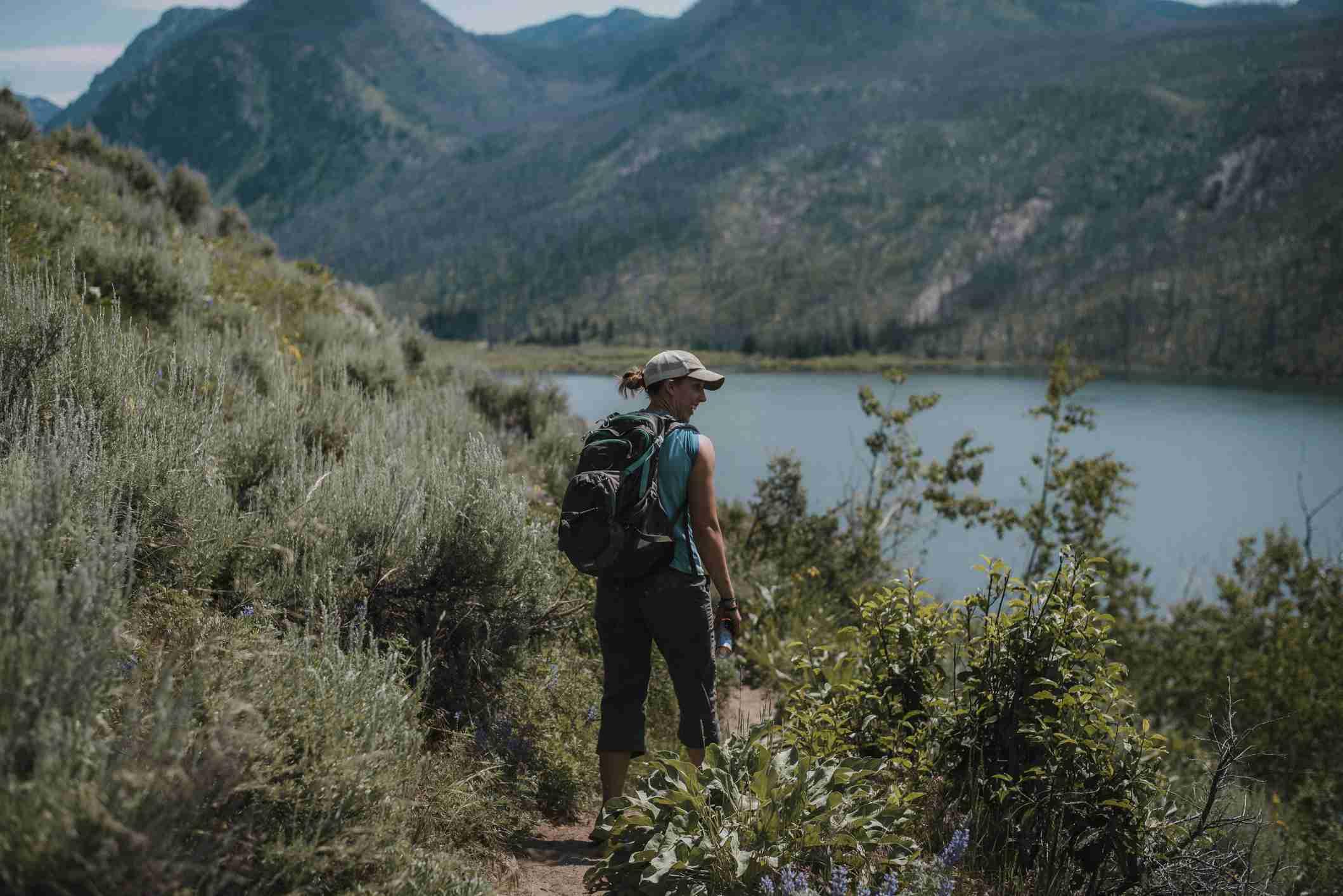 Female hiker standing in field of plants in Wyoming