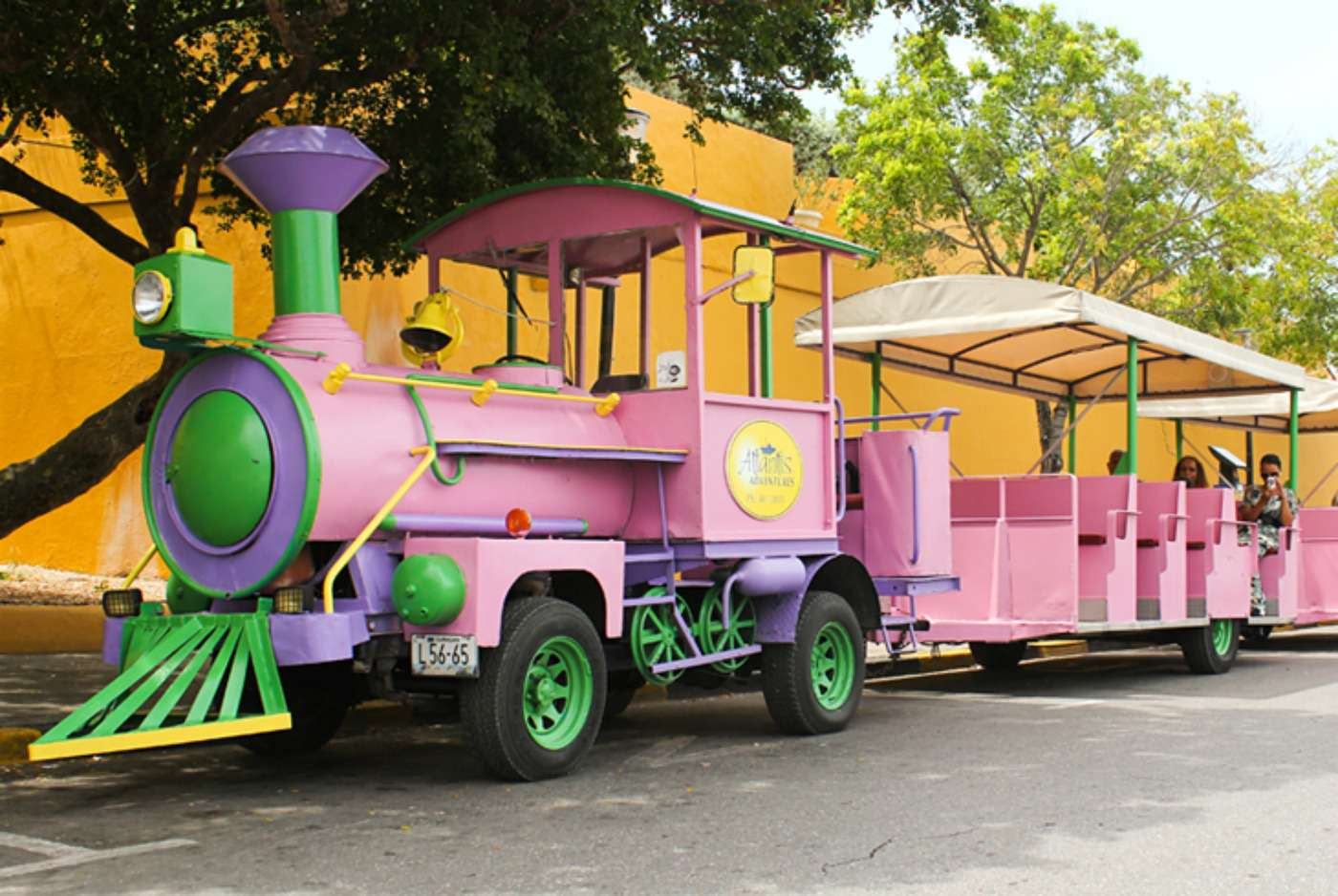 Curaçao Trolley, painted in pink, purple, and green, parked at a stop on its route while people sit in the back.