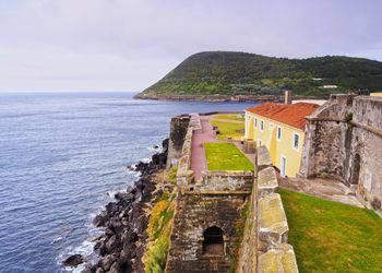 Portugal, Azores, Terceira, Angra do Heroismo, View of Fort Sao Sebastiao and Monte Brazil in background