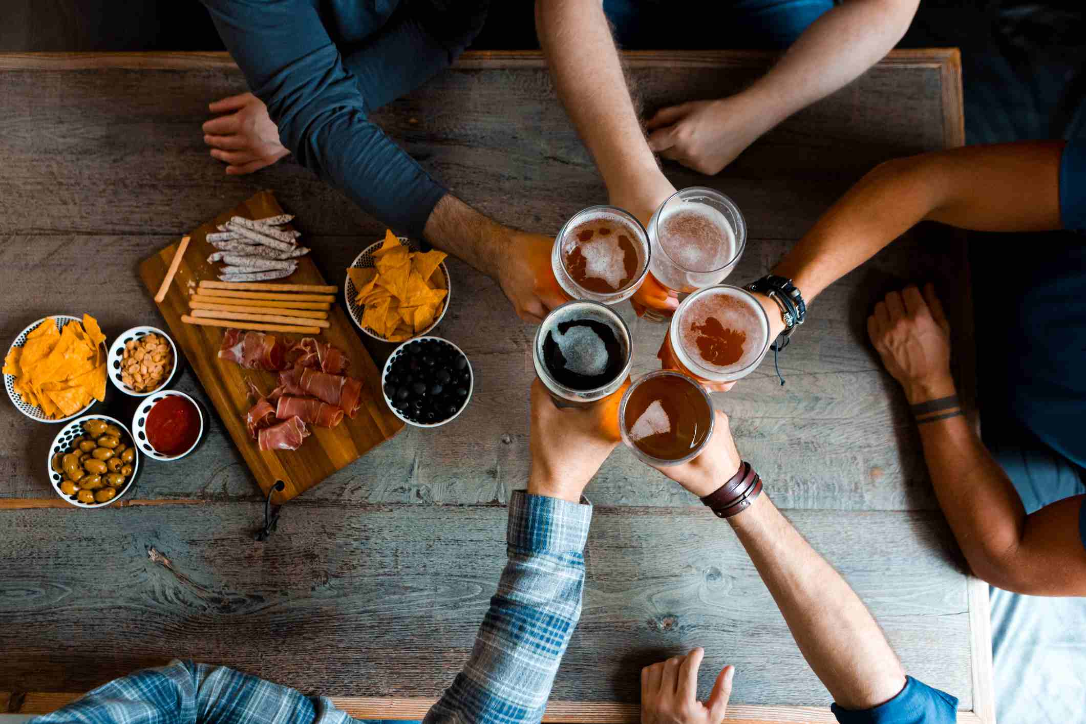 Top view of friends toasting with beer above the table in pub
