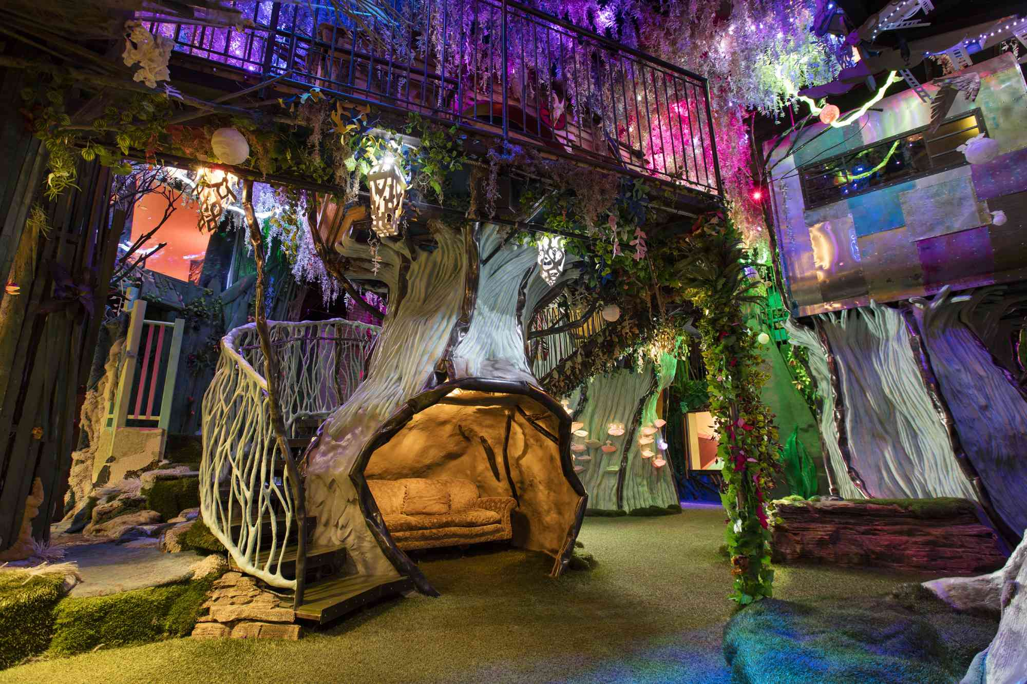 Part of Meow Wolf's House of Eternal Return. There is an artifical tree with a couch nestled into the base. A staircase wraps around the tree to a second level. The second level has vines wrapped around the metal fence