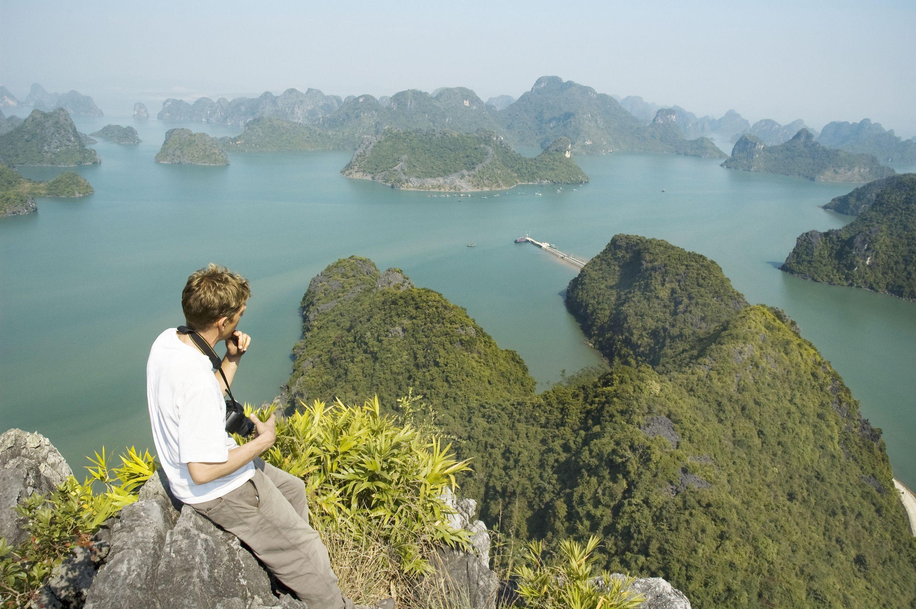 Hiker viewing Ha Long Bay from atop a crag