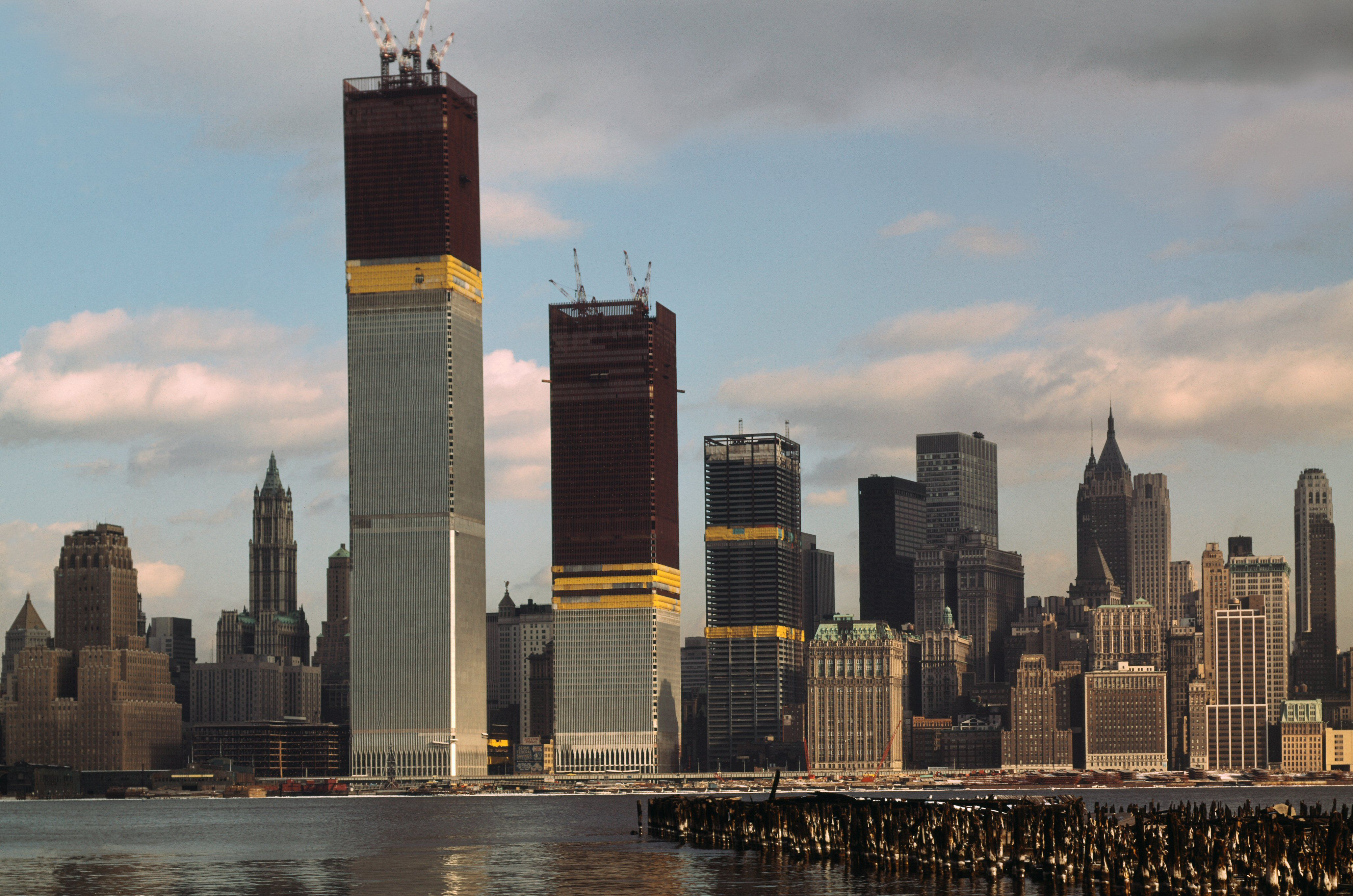Views of the World Trade Center (both of its twin towers still under construction) and Manhattan skyline views taken from New Jersey shore