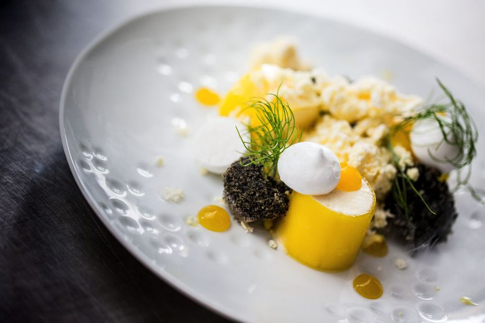 Artfully plated white and and yellow dish on a white plate